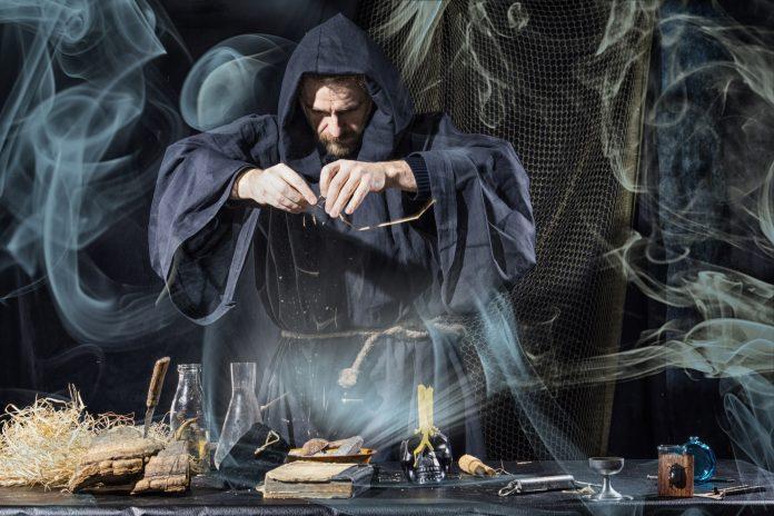 Magie noire sorcellerie magicien devant une table