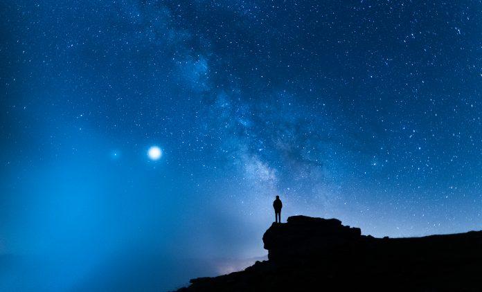 Personne contemplant le ciel étoilé depuis une montagne