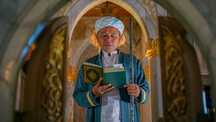 Imam en prière avec un Coran dans les mains